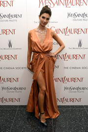 Teresa Moore looked alluring in a floor-sweeping coral wrap dress by Kora Rae during the 'Yves Saint Laurent' premiere.