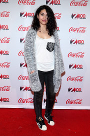 Alessia Cara kept things cozy with her loose grey cardigan, tee, jeans, and striped black and white crosstrainers at the Jingle Ball All Access Lounge.