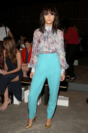 Cara Santana topped off her pants with a demure print blouse.