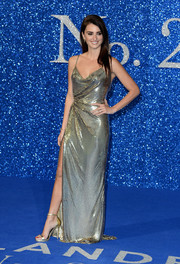 Penelope Cruz kept the shine coming with a pair of gold ankle-strap sandals.