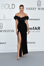 Karlie Kloss looked absolutely divine at the amfAR Cinema Against AIDS Gala in a black Marchesa off-the-shoulder gown with a petal-embellished neckline and a thigh-high slit.