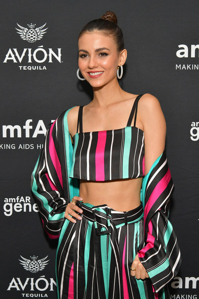 Victoria Justice flaunted her flat abs in a striped satin crop-top by Victoria Hayes at the amfAR GenCure Solstice 2018.
