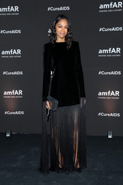 Zoe Saldana attended the amfAR Gala in Mexico wearing a black Saint Laurent velvet dress with fringe detailing.