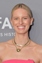 Karolina Kurkova accessorized with an eye-catching gold necklace by Ana Khouri.
