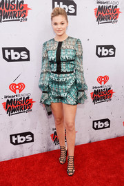 Olivia Holt flaunted some leg in a printed blouson-sleeve romper by Genny at the iHeartRadio Music Awards.