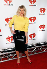 At the iHeartRadio music festival, Fergie donned a yellow sweater paired with a chic leather pencil skirt. She finished off the look with red peep-toe pumps.