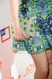 Bella Thorne carried a cool silver and green beaded clutch that complemented her green floral dress really well.