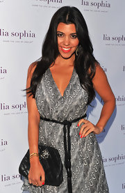 Kourtney Kardashian upped the glamour of her printed maxi dress at the Lia Sophia launch with a black quilted leather clutch.