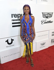 Justine Skye paired her vibrant dress with simple black ankle-strap sandals.