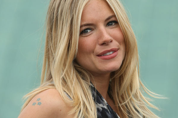 Sienna Miller has several small and girly tattoos including a lip stain on