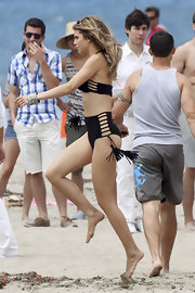 AnnaLynne McCord got playful in the sand on the set of 90210 wearing a tasseled black bikini. The young starlet showed off her lovely figure and highlighted California girl locks.
