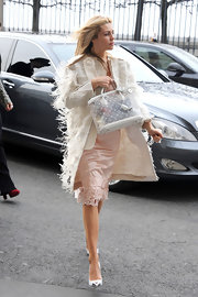 Abbey Clancy accessorized her whimsical feathered outfit with a clear Louis Vuitton tote.
