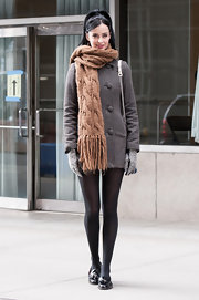 Krysten Ritter chose this gray tweed coat to pair with an oversized knit scarf while on set of 'Assistance.'