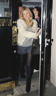 Sienna wears a fluffy coat over a t-shirt and shorts for her outing in London.