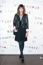 Alexa Chung attended a fashion event wearing a pair of black patent leather sandals.