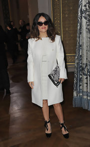 Salma Hayek kept things sophisticated in a white collarless coat and matching sheath dress at Paris Fashion Week.