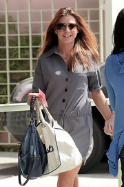 """Alyson Hannigan showed off her cute metallic shoulder bag, which worked well with her grey romper. She also carried the popular """"Im Not A Plastic Bag"""" tote to show her support for environmental causes."""