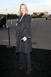 Lisa Kudrow exuded an air of mystery in her all-black ensemble, topped off with a chic iridescent trenchcoat.