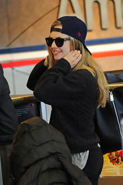 Amanda Seyfried sported this navy baseball cap backward for her cool and casual travel look.
