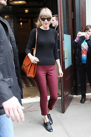 Taylor Swift chose a pair of deep red skinny pants for her retro-inspired daytime look.