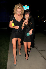 Angel stepped out with her sister wearing a pair of feather-embellished, black, peep-toed pumps. The sexy shoes complemented her textured coat and darkened do.