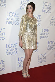 Anne Hathaway paired her glimmering Oscar de la Renta dress with platform metallic sandals for a look that truly glows!