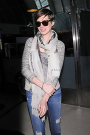 Anne Hathaway traveled in style with this gray striped cardigan, which she paired with a print scarf.