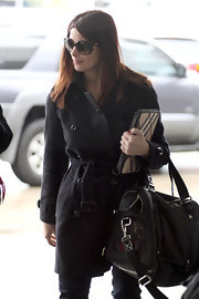 Ashley looks classic at the airport in a black trench.