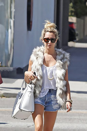 Ashley Tisdale stuck to her signature hippie-style with this long fur vest.