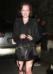 Elisabeth Moss accessorized her monochromatic look with a posh black leather back with patent corners.