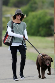 Sharni Vinson embraced layers, while walking her dog in a sage green T-shirt worn over a white long-sleeve.
