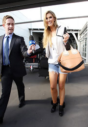 Delta Goodrem gave her shredded cut offs a luxe touch with a beige leather purse with white tonal straps.