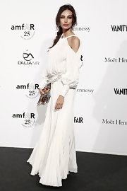 Madalina Ghenea stepped out at the amfAR Milano event wearing a long white dress with shoulder cutouts.