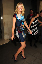 Rosamund Pike paired a bold print mini dress with stud-embellished purple satin pumps.