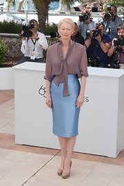 Tilda Swinton paired her blousy top with this streamlined blue iridescent pencil skirt.