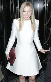 Kristen Bell carried a red rhinestone embellished clutch for a pop of color against her pristine white coat.