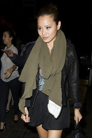 Jamie is bundled up in a thick olive knit scarf and a cropped leather jacket.