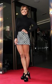 Caroline Flack opted for a chic mod-inspired look when she paired a classic black turtleneck with a houndstooth mini skirt.