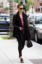 Charlize looked chic and warm in her leather-sleeved open-front cashmere cozy.