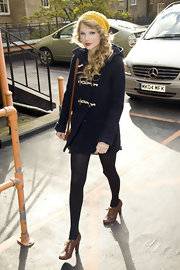 Taylor looked ready for fall in a toggle fastened navy blue pea coat. She completed her look with lace up ankle boots and a knit beanie.