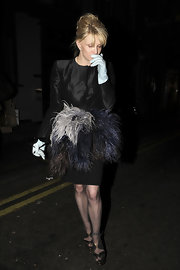 Courtney Love donned a crisp black evening jacket adorned with feathers for her outing in London.