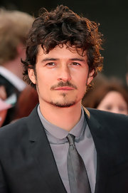 Orlando wore messy curls with a gray suit on the red carpet in London.