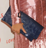 Hannah Bronfman added a splash of purple to her all pink look with this oversized purple clutch.