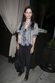 Courtney donned a silky ruffle blouse with black skinny jeans at the Roosevelt in Hollywood.