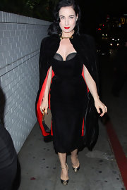 Dita Von Teese chose a black velvet cape with red lining for her retro-gothic look.