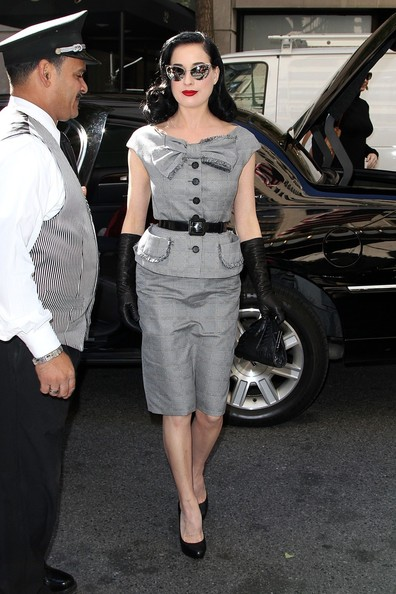 Dita Von Teese smiles and waves while signing autographs as she leaves the