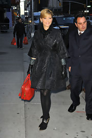 Elizabeth Banks bundled up in a brocade coat paired with black ankle boots.