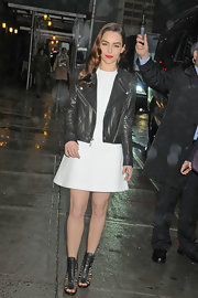 Emilia Clarke paired an edgy leather jacket with a pretty white frock for an unexpected but cool look.