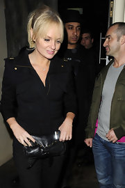 Emma carried a gold-studded, leather envelope clutch when she stepped out for the night in London.