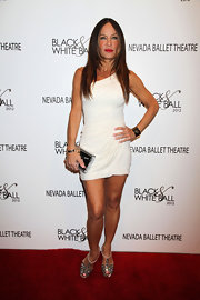 Robin Antin added shine to a Grecian-inspired little white dress with a silver clutch and matching heels.